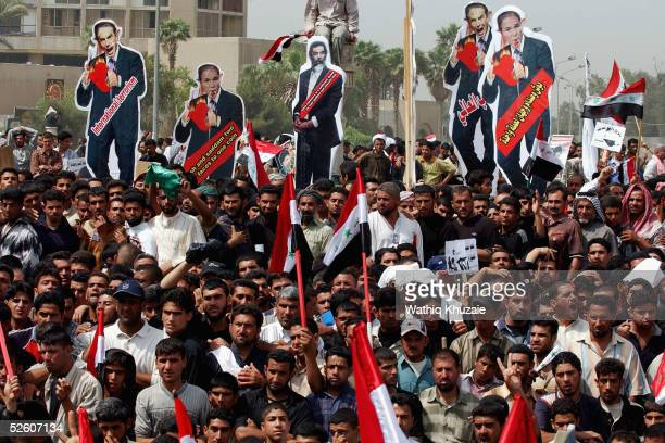 Iraqi supporters of Shiite cleric Moqtada alSadr carry cut outs of US President George W Bush former Iraqi President Saddam Hussein and British Prime...