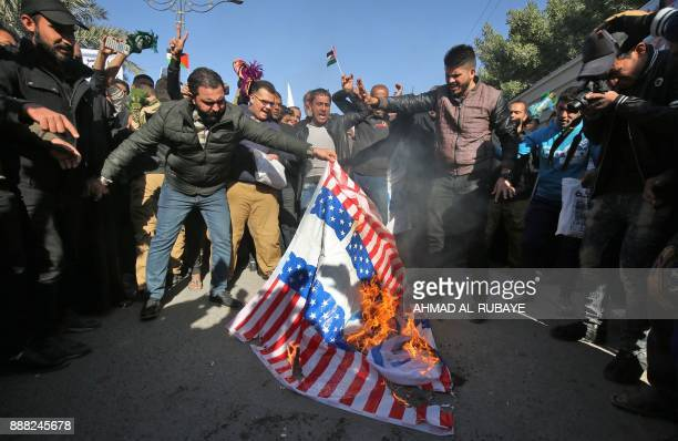 Iraqi supporters of Shiite cleric Moqtada alSadr set US and Israeli makeshift flags on fire during a protest in Baghdad after the Friday noon prayers...
