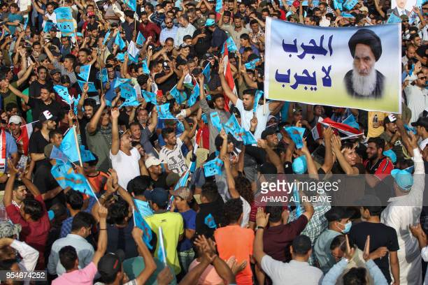 Iraqi supporters of shiite leader Moqtada Sadr raise a poster showing the country's top Shiite authority, Ayatollah Ali Sistani with a caption next...