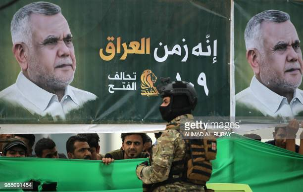 Iraqi supporters of the Fateh Alliance a coalition of Iraniansupported militia groups listen to a speech by Hadi Amiri head of the Iranianbacked Badr...