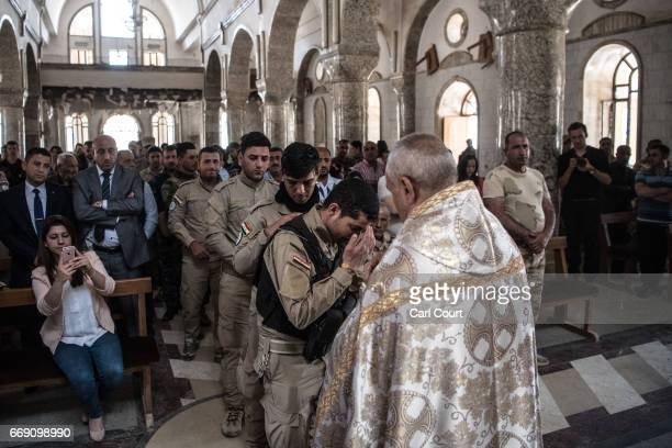 Iraqi Syriac Christian priest Charbel Aesso gives the Eucharist during an easter service at Saint John's Church in the nearly deserted predominantly...