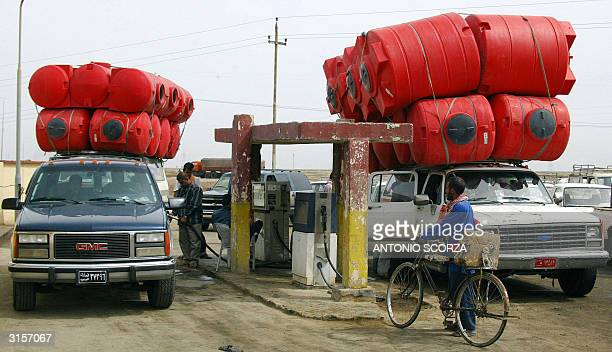 Iraqi taxis carrying tanks line up to refuel 27 Mar 2004 at a gas station on the in Nasiriyah some 400km south of Baghdad Iraq imposed gasoline...