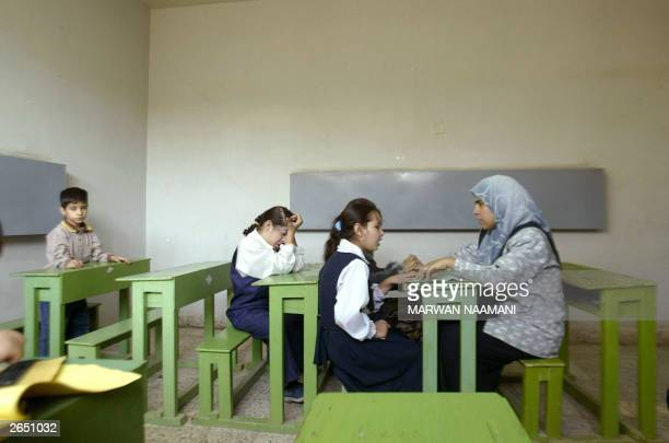 Iraqi teacher Huda Jassim sits in front of eightyear old Leukemia patient Maryam long the symbol of Iraqi children's ordeal from UN sanctions and the...