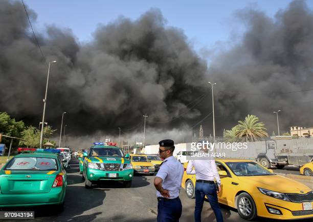 Iraqi traffic policemen stand outside the country's biggest ballot warehouse where votes for the eastern Baghdad district were stored as a column of...