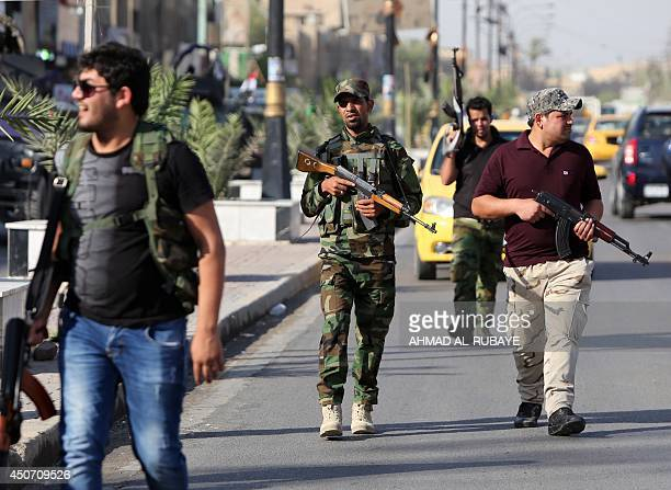 Iraqi tribesmen carry their weapons as they gather to show their readiness to join Iraqi security forces in the fight against Jihadist militants who...