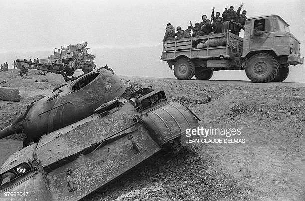 Iraqi troops flash Vsigns as they move past a crushed Sovietmade tank on their way to the front line 18 March 1985 during the battle for the city of...