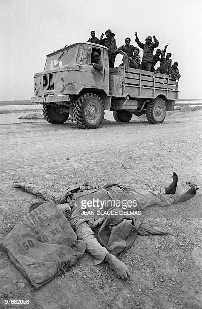 Iraqi troops flash Vsigns as they move past a killed Iranian soldier on their way to the front line 18 March 1985 during the battle for the city of...