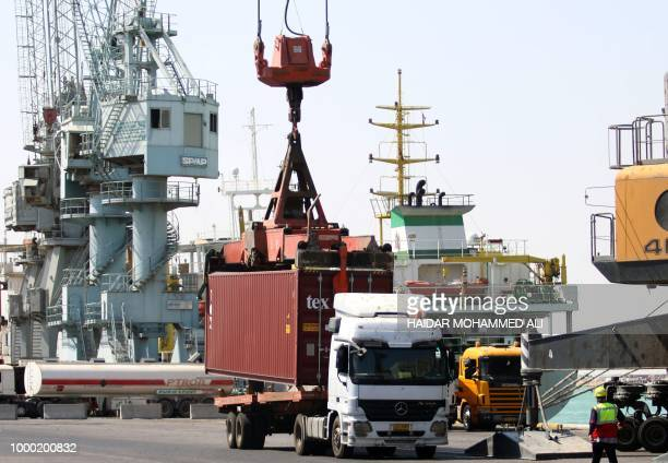 Iraqi trucks wait to be loaded with containers at the harbour of Umm Qasr south of Basra in southern Iraq after the port reopened on July 16...