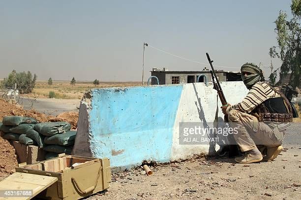 Iraqi Turkmen Shiite fighter, who volunteered to join the government forces, holds a position on August 4, 2014 in Amerli, some 160 kilometres north...