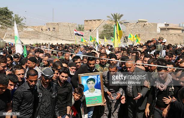 Iraqi Turkmen Shiite mourners gather during a mass funeral for 22 members of the Popular Mobilisation units, who were killed the month before during...
