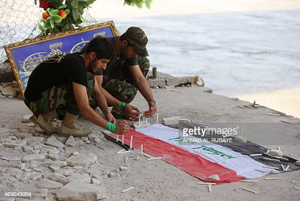 Iraqi university students light candles on the Tigris river waterfront in Tikrit on April 9 which is believed to be the place of a June 2014 massacre...