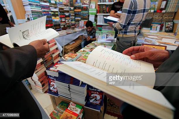 Iraqi visitors look at books on the opening day of the 6th Najaf's book fair on March 7 2014 at the shrine of Imam Ali in the Iraqi central city of...