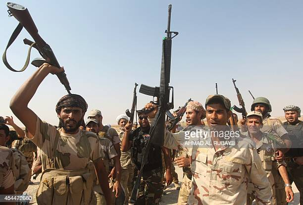 Iraqi volunteer fighters celebrate the breaking of the jihadist siege on the Shiite town of Amerli as they advance towards the town from the position...
