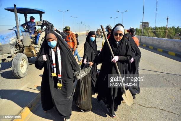 Iraqi volunteers clean up the streets of the central city of Najaf on December 5, 2019 following anti-government protests. - The protest movement is...