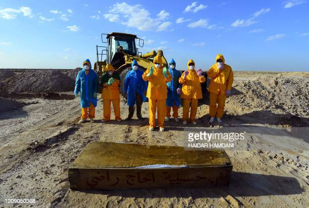 Iraqi volunteers in full hazmat gear pray over the coffin of a fiftyyearold victim of the COVID19 virus before her burrial at a cemetary specifically...