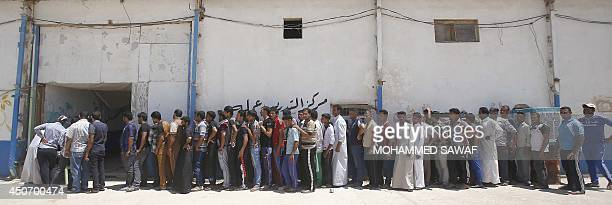 Iraqi volunteers queue to collect their uniforms following a speech by Iraqi Prime Minister Nuri alMaliki who announced that the Iraqi government...