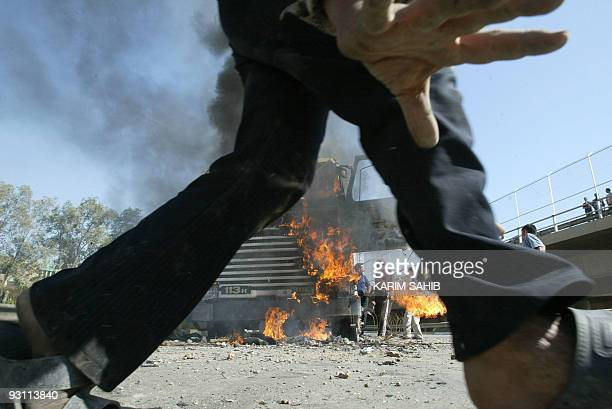 A Iraqi walks near a burning truck attacked by insurgents on the road leading to Baghdad's International Airport 10 April 2004 in Baghdad The truck...