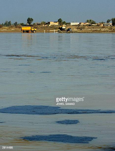 Iraqi water tankers collect water from the Tigris river as large black plates of oil flow on the muddy water of the river in Tikrit, some 180...
