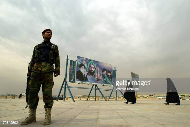 Iraqi woman and a solider are seen near a picture that shows Ayatollah Muhammad alSad Imam Hussein Muhammad Baqir alSadr and Moqtada alSadr on...
