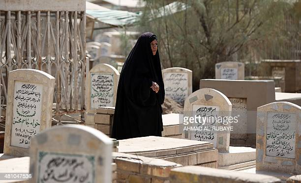A Iraqi woman arrives to visit the graves of loved ones at a cemetery in the capital Baghdad on July 17 2015 on the first day of Eid alFitr holiday...