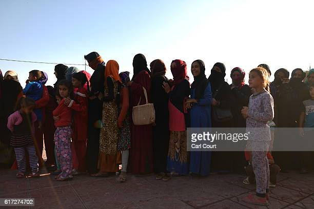 Iraqi women and children queue for food in Debaga refugee camp where people displaced by fighting in and around Mosul have sought shelter on October...