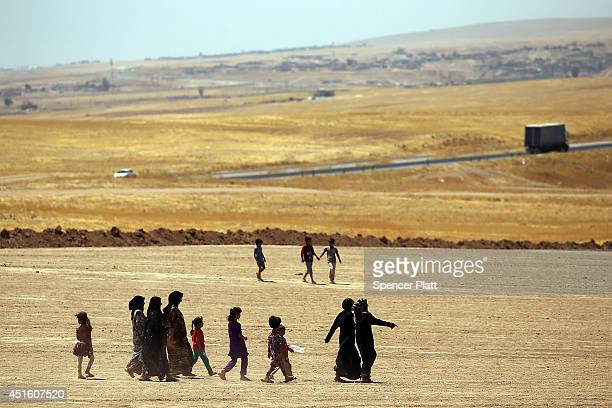 Iraqi women and children walk towards a camp entrance as thousands of Iraqis who have fled recent fighting in the cities of Mosul and Tal Afar try to...