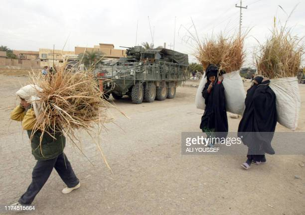 Iraqi women carrying bags of reed walk past an armoured vehicle patrolling in the village of alHadid on the outskirts of the restive city of Baquba...
