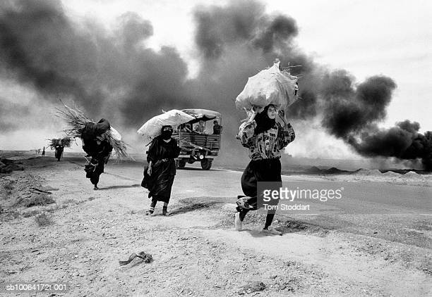 Iraqi women carrying firewood walk through thick smoke from burning oil in an oil field near Basrah Southern Iraq a week after British troops freed...