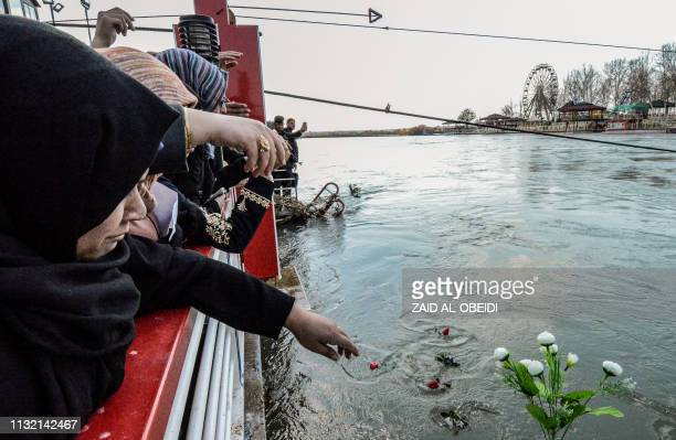Iraqi women cast flowers into the Tigris river in remembrance for the victims of the capsized ferry in the northern Iraqi city of Mosul on March 22...