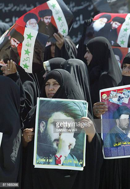 Iraqi women hold pictures of radical Shiite Muslim cleric Moqtada Sadr and his assassinated father Mohammed Sadeq Sadr during a massive demonstration...