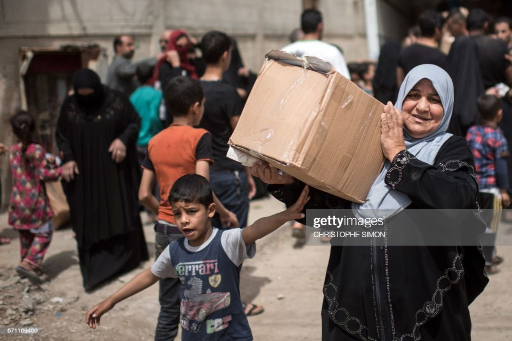 Iraqi women in west Mosul receive aid packages given by volunteers from the eastern side on April 21, 2017, as Iraqi forces continue the offensive to retake the city from Islamic State (IS) group fighters. /