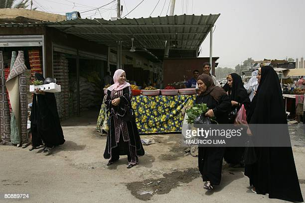 Iraqi women leave a market area after buying some vegetables during a patrol by US soldiers from 3rd Battalion 320th Field Artillery Regiment in...