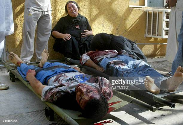 Iraqi women mourn over the bodies of their relatives outside the morgue of a hoapital in Baquba north of Baghdad 16 August 2006 Two Iraqis were...
