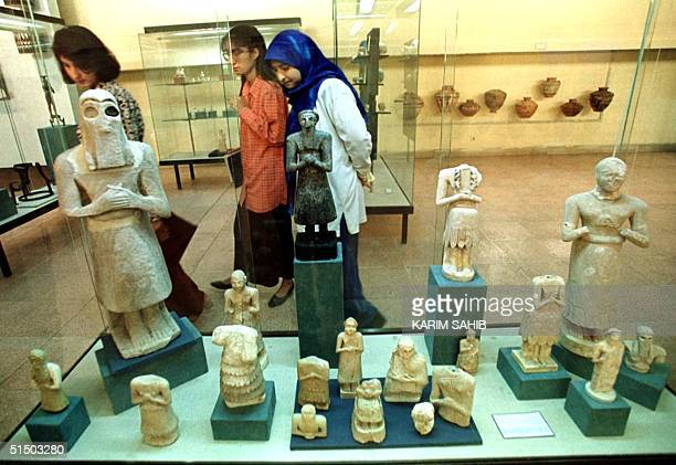 Iraqi women peruse Assyrian artefacts dating back to 2800 BC at the Baghdad Museum 29 April 2000 on the day of its reopening The museum which houses...