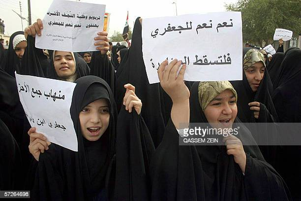 Iraqi women raise leaflets that read 'Yes for Jaafari No for the conspiracy' during a demonstration in the holy city of Najaf south of Baghdad 06...