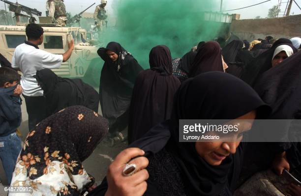 Iraqi Women scramble for cover as American soldiers from the First Cavalry Division fire gas onto a desperate crowd during a propane distribution in...
