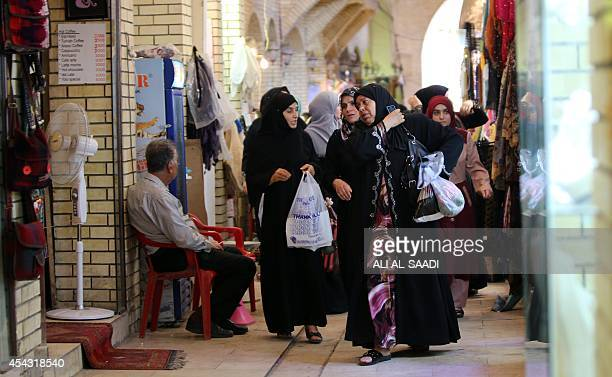 Iraqi women shop at market near the citadel in Arbil the capital of the autonomous Kurdish region of northern Iraq on August 28 2014 About 700000...