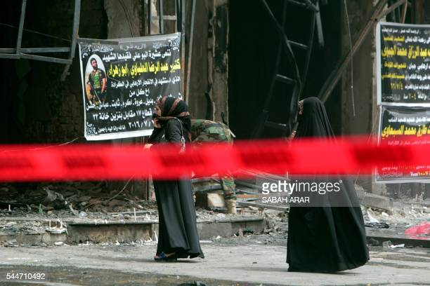 TOPSHOT Iraqi women stand on July 4 2016 at a site barricaded with a security red tape in Baghdad's Karrada neighbourhood a day after an attack took...