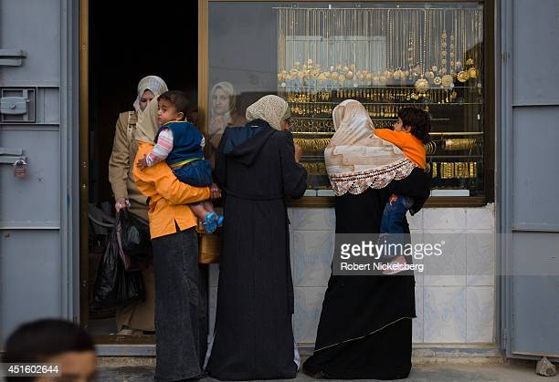Iraqi women stand outside a gold shop February 17 2007 in Husayba Iraq Husayba a strategic border crossing with Syria along the Euphrates River was...