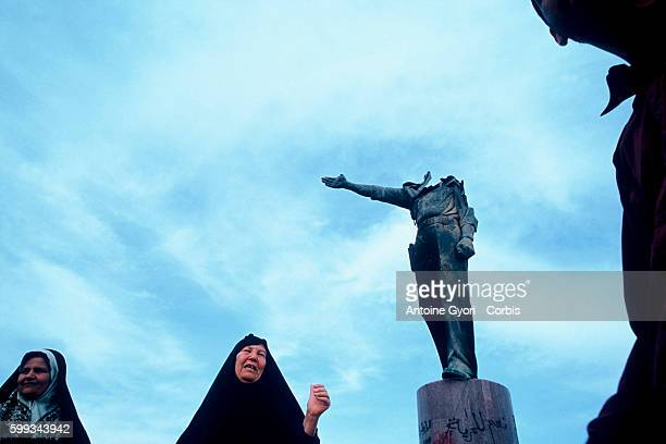 Iraqi women standing in front of a decapitated statue of Saddam Hussein