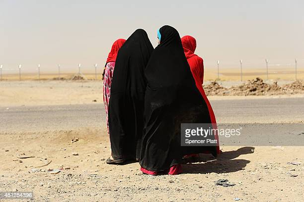 Iraqi women wait outside of a temporary displacement camp for Iraqis caughtup in the fighting in and around the city of Mosul on June 26 2014 in...