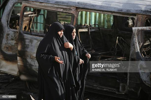 Iraqi women walk at the site of a car bomb explosion in the mainly Shiite Sadr City district in Baghdad on June 18 2014 which killed at least seven...