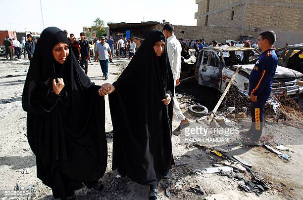 Iraqi women walk at the site of a twin suicide bombing attack claimed by the Islamic State group in the southern Iraqi city of Samawah situated deep...