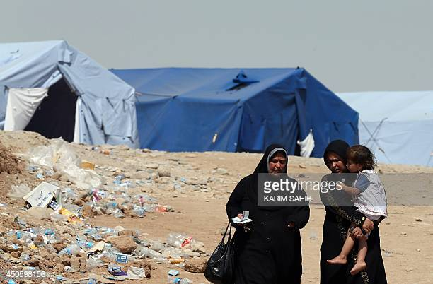 Iraqi women walk in the temporary camp set up to house civilians fleeing violence in Iraq's northern Nineveh province in Aski kalak 40 kms west of...