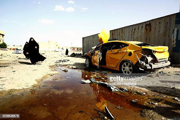 TOPSHOT Iraqi women walk past a damaged car following a twin suicide bombing attack claimed by the Islamic State group in the southern Iraqi city of...
