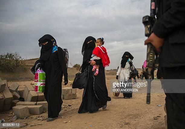 TOPSHOT Iraqi women walk past a security forces member as they flee to an area held by the Iraqi Special Forces 2nd division in the Samah...