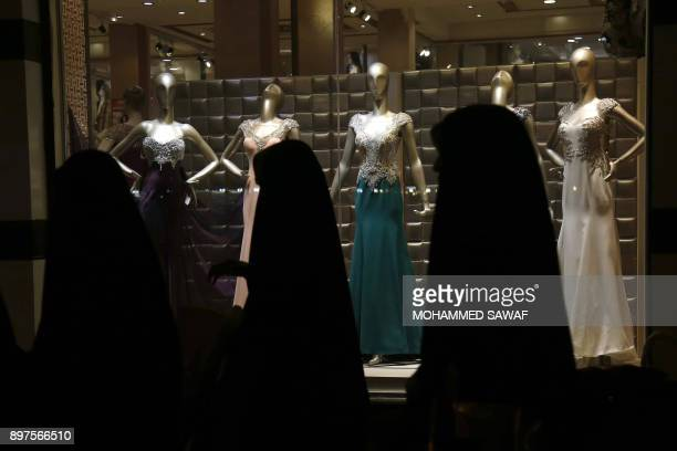 Iraqi women walk past a window display of a shop selling women's clothes in the Shiite holy city of Karbala on December 22 2017 Activists in Iraq's...