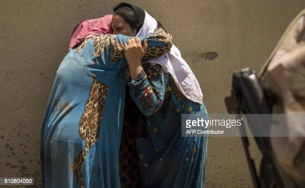 Iraqi women who fled the fighting between government forces and Islamic State group jihadists in the Old City of Mosul cry as they stand in the...