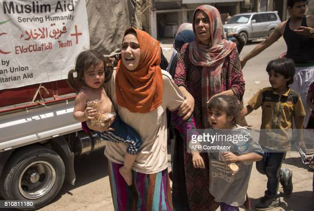 Iraqi women who fled the fighting between government forces and Islamic State group jihadists in the Old City of Mosul arrive in the city's western...