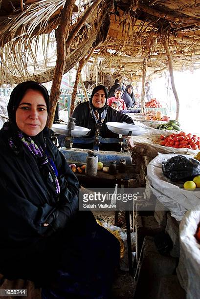 Iraqi women who work as vendors smile at the camera while they are waiting for customers to buy their products November 24 2002 in the town of...